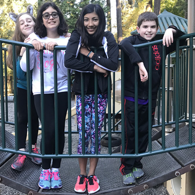 Four Middle School students pose for a photo on the play equipment bridge.